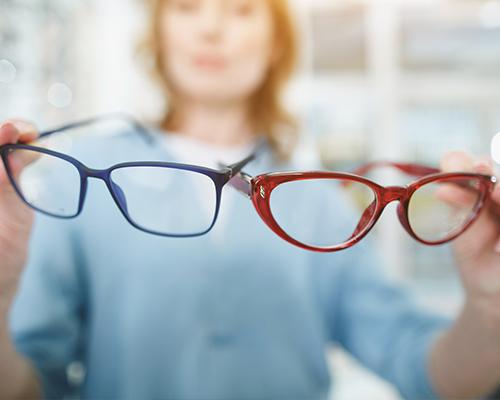 Deux paires de lunettes tenues par une femme
